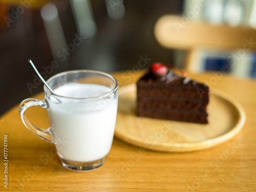Fotobehang Milkshake glass of milk with chocolate cakes on top red cherry background in wooden plate on wood table