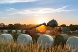 Im Sonnenuntergang lädt ein Traktor Ballen vom Anhänger aufs Feld um