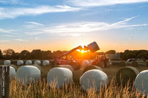 Aluminium Trekker Im Sonnenuntergang lädt ein Traktor Ballen vom Anhänger aufs Feld um