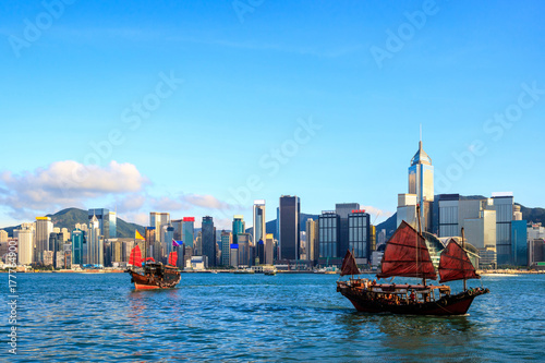 Hong Kong skyline cityscape, Tourist junk boat at Victoria Harbor in evening Poster