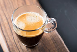 Glass of americano espresso fresh made dark black strong coffee on wooden board table, thick froth foam in cafe, morning refreshing hot drink caffeine, copy space for text