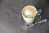 hot coffee latte with beautiful foam art heart shape on wooden table at coffee shop