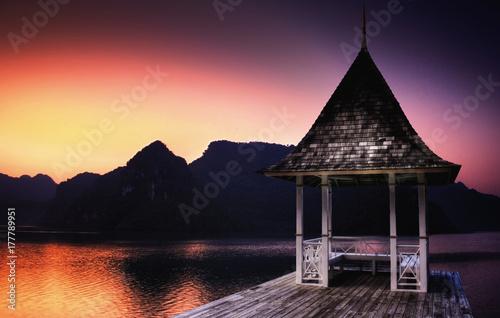 Fotobehang Pier Small building next to large lake during sundown