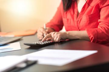 Businesswoman using a calculator, light effect