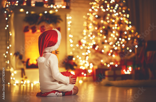 Leinwandbild Motiv child girl  sitting  back in front of  Christmas tree on Christmas Eve