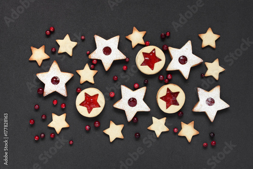 Traditional Linzer cookies - stars with red jam and cranberry on the black backg Poster
