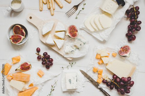 Fototapeta Various types of cheese with fruits and snacks on the wooden white table. Top view