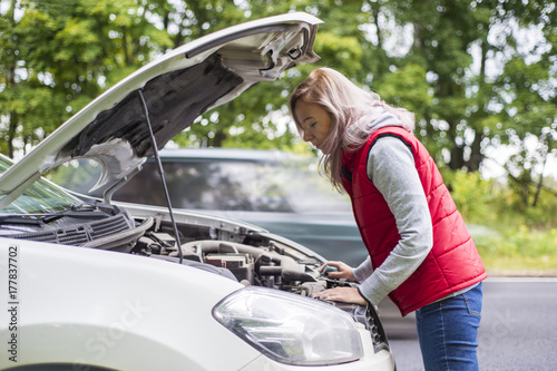 young brunette girl with a broken car with open hood Plakát