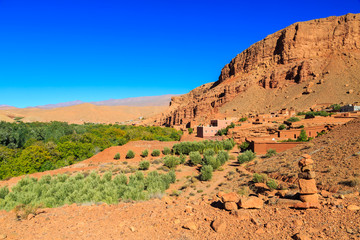 Landscape of a typical moroccan berber village with oasis in the valley