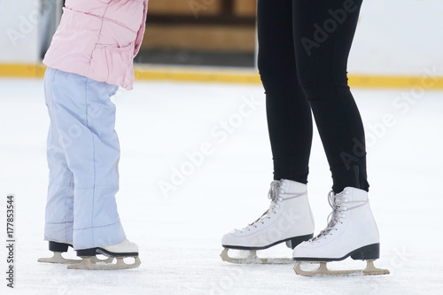 the legs of a man skating on an ice rink Poster