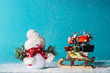 Snowman and sledge with christmas gifts on cyan background
