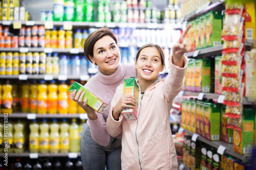 attentive woman with daughter choosing refreshing beverages in supermarket Poster