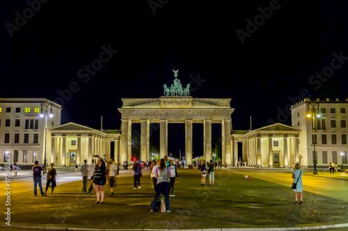 Платно Beleuchtetes Brandenburger Tor in Berlin bei Nacht im Sommer mit Passanten im Vo