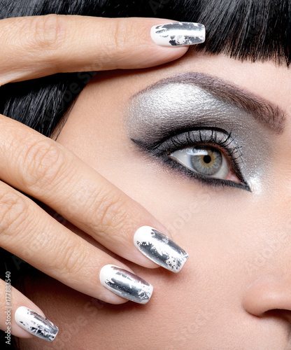 Aluminium Manicure Beautiful girl with the silver makeup and nails.