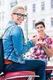 Junge Leute essen Currywurst Pommes in Berliner Imbissbude
