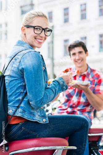 Foto op Plexiglas Berlijn Junge Leute essen Currywurst Pommes in Berliner Imbissbude