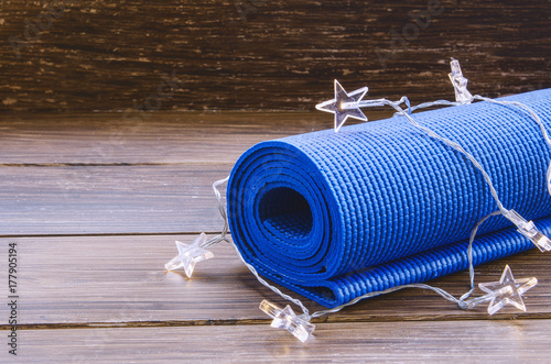 Fototapeta Blue exercise mat with Christmas garland on wooden background. Training on Christmas Day concept. Sport xmas concept. Copy space.