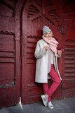 Cheerful senior lady leaning on door of historic building - 177908943