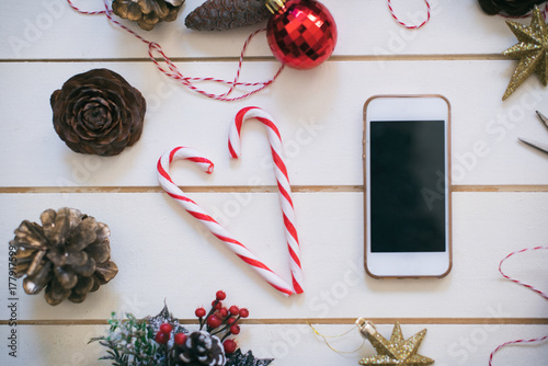 Mobile phone on wooden background with Christmas gifts Poster