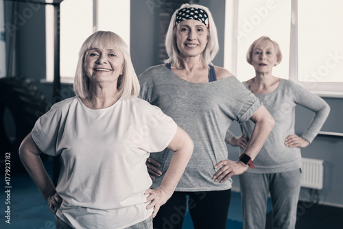 Three elderly women standing one behind another in gym