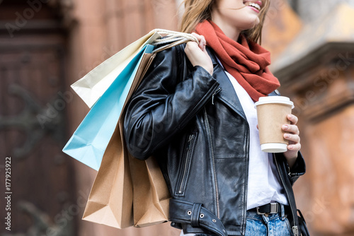 woman with shopping bags and coffee to go