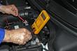 Mecánico comprobando el voltaje de la batería del coche
