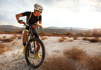Young cyclist resting after riding a mountain bike over the desert.Sunset.
