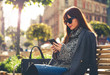 Pretty woman using tablet or ebook reader sitting in town, urban scene - 177934704
