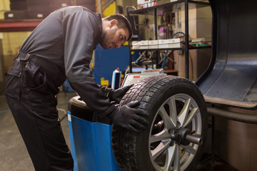 auto mechanic balancing car tire at workshop