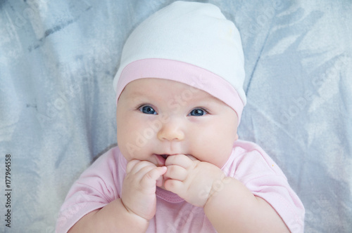 Baby girl portrait with hand in mouth lying on bed Poster