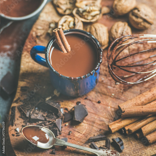 Aluminium Chocolade Rich winter hot chocolate with cinnamon sticks and walnuts in blue enamel mug on wooden board over grey concrete background, selective focus, square crop