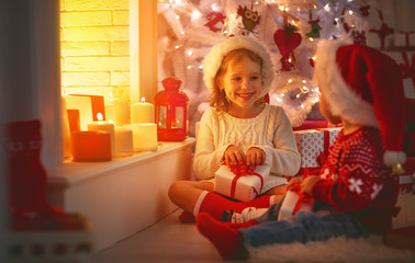 happy children with christmas presents near Christmas tree and fireplace.