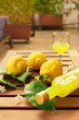Leinwandbild Motiv Lemonade or limoncello in a glass bottle, glasses, lemons with leaves on a wooden table on the terrace. Close up.