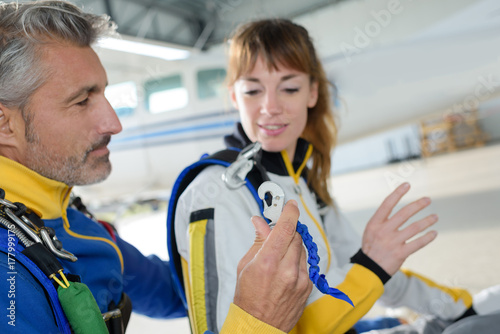 Instructor showing equipment to skydiver Poster