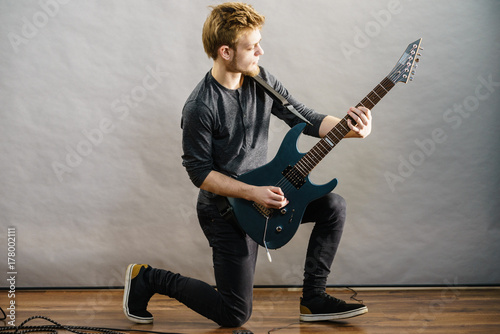 Young man playing electric guitar Poster