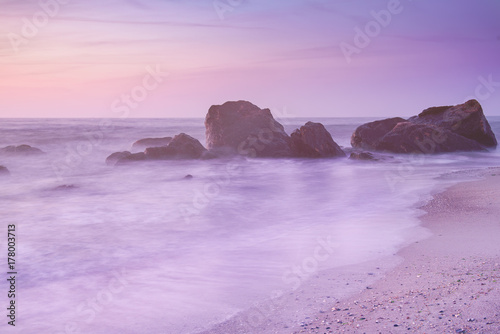 Foto op Plexiglas Purper Summer seasonal natural vacation background. Romantic morning at sea. Big boulders sticking out from smooth wavy sea. Pink horizon with first hot sun rays. Long exposure.