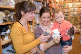 mother and daughter with attractive vendor in toy store - 178005933