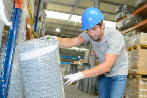 Worker checking reference on roll of fencing
