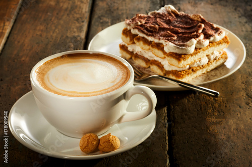 Cup of milk coffee with piece of cake