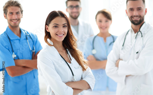 Attractive female doctor with medical stethoscope in front of medical group © FotolEdhar