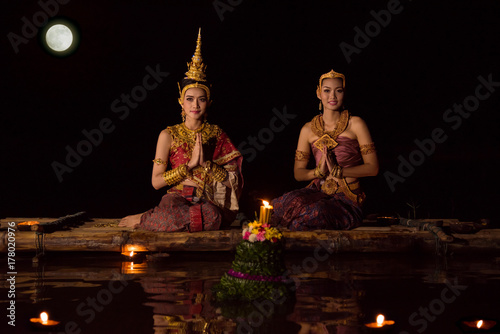 Beautiful asian women in traditional Thai dress sitting on floating raft in Loy Poster