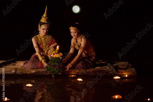 Beautiful asian women in traditional Thai dress floating krathong in Loy krathon Poster
