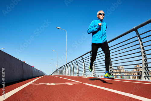 Poster Low angle view of concentrated senior sportsman jogging outdoors and enjoying sunny warm day, full length portrait