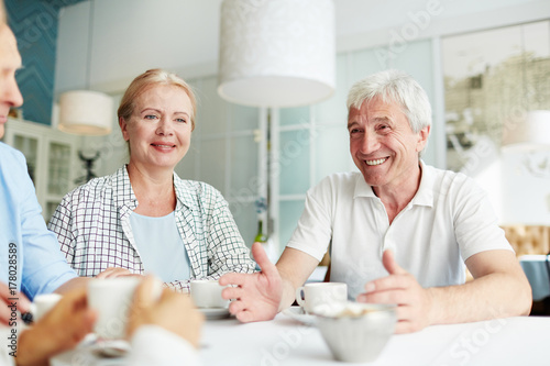 Cheerful senior couple talking to their friends at leisure in cafe Plakat