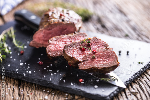 Foto op Canvas Steakhouse Beef Steak. Roasted Beef steak with salt pepper thyme on rustic wooden table