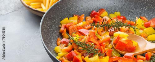 Cooking bell peppers with rosemary in skillet as sauce for italian pasta - 178044538
