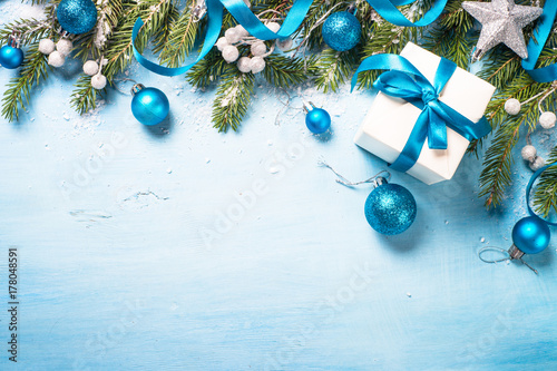 Christmas background on blue. Present gift box, branch, balls and decorations top view.
