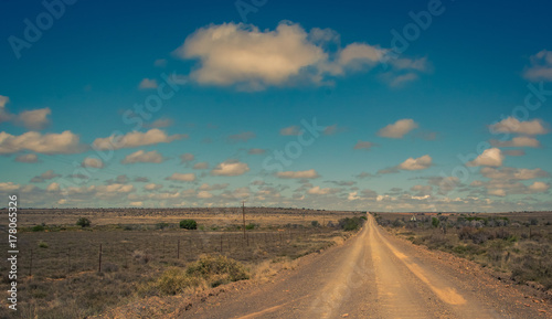 Fotobehang Nachtblauw A dry dusty dirt road leads straight to the horizon in the arid Karoo area of South Africa