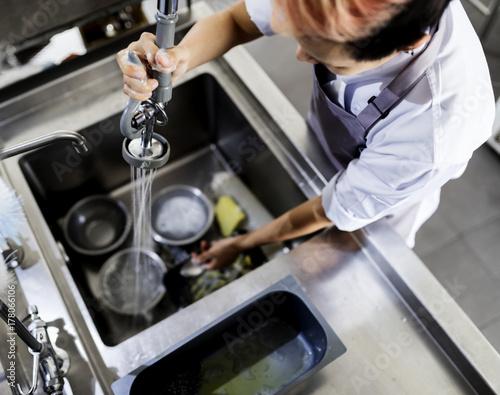 Top view of kitchen staff washing utensils at sink