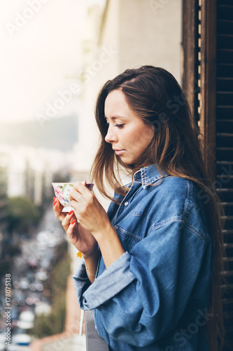 31aa51182d2 A beautiful and young Caucasian girl in big jeans shirt is holding a large  cup of